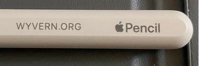 A second-generation Apple Pencil with wyvern dot org printed on it.